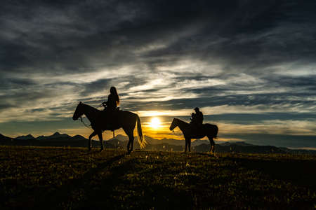 Sunset on horseback of the young family in the Western Sierra of Jalisco. 免版税图像