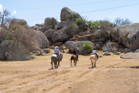 The family rides horses on the rocks of Tapalpa Jalisco. Standard-Bild