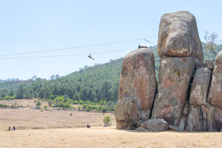 The young woman is reaching the rocks on the zip line of Tapalpa Jalisco.