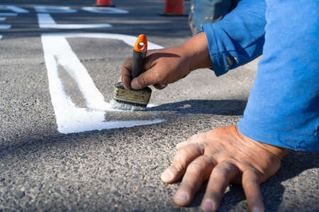 The worker is making a letter from the road sign on the avenue.