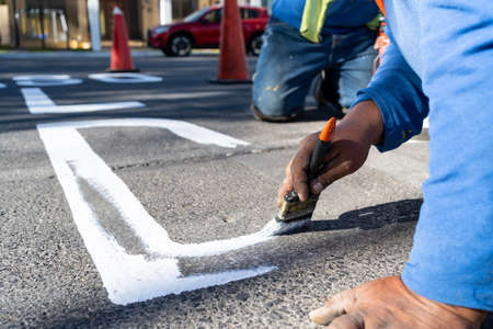 The worker is finishing making a letter of the traffic sign.