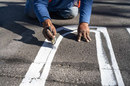 The worker is leaning with his hand to paint the signs on the street. 免版税图像