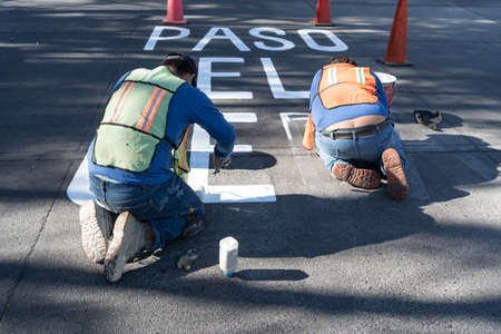 Two workers are finishing making the traffic signs for the street. 免版税图像