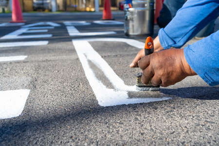 The worker is making a letter from the road sign. 免版税图像