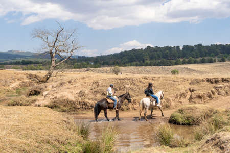 Two young men with their horses are coming out of a stream.