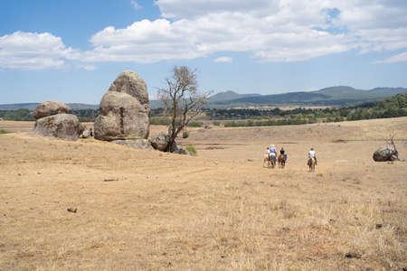 A family rides horses on the rocks of Tapalpa Jalisco. 免版税图像