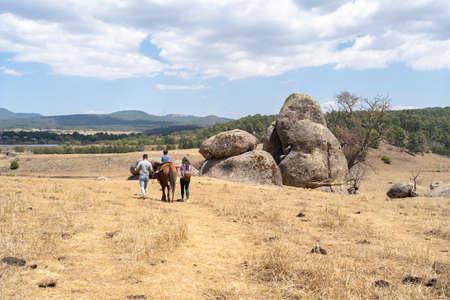 A family walks on the rocks of Tapalpa Jalisco.