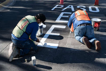 Two workers are painting the road signs.