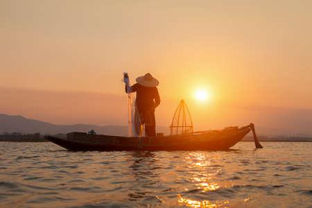 Silhouettes of the traditional stilt fishermen at sunset. Foto de archivo