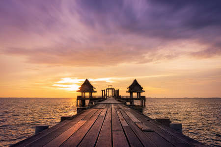 Ponte de madeira de Crepúsculo na atração turística do templo Djittabhawan em Pattaya, Tailândia Foto de archivo - 84104560