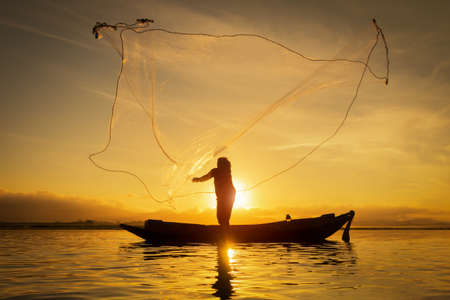 Silhouette of asian fisherman on wooden boat ,fisherman in action throwing a net for catching freshwater fish in nature river, traditional fishermen at the sunset in thailand