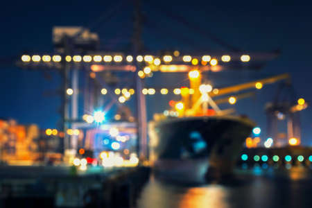 Blur bokeh of harbor with large ship and crane at night Foto de archivo