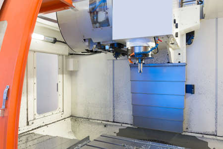stainless: cnc metal working machine with cutter tool during metal detail milling at factory