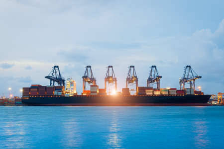 unloading: Logistics and transportation of International Container Cargo ship with ports crane bridge in harbor for logistic import export background and transport industry.