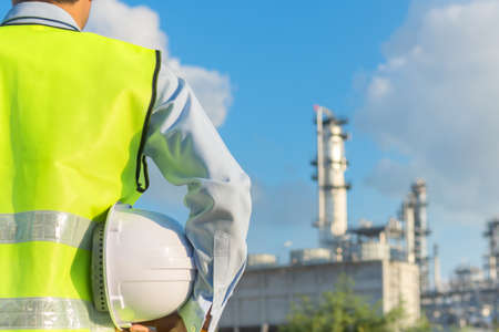 Engineering man standing with white safety helmet near to oil refinery Foto de archivo