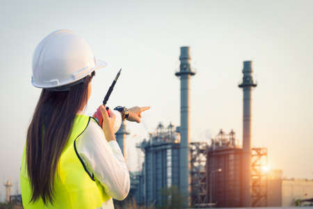 Asia woman Engineer working in a power plant with talking on the walkie-talkie for controlling work