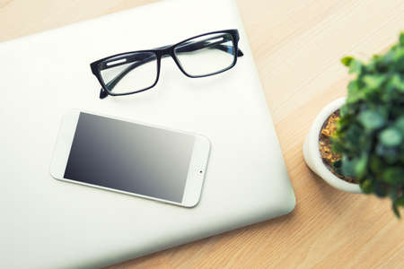 glasses and tablet on a wood table