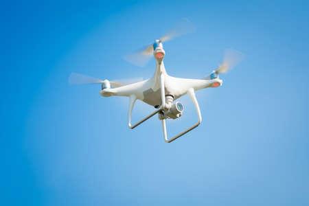 Drone blanco flotando en un cielo azul brillante Foto de archivo - 85037424
