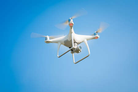 white drone hovering in a bright blue sky Stock Photo