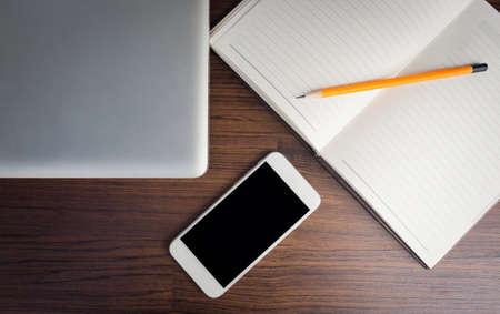 tablet black screen on wood desk on top view Foto de archivo