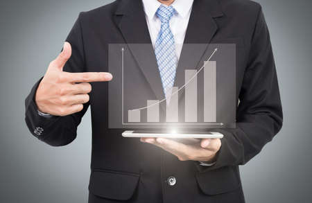 businessman pointing on financial symbols coming from screen Foto de archivo