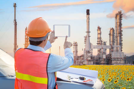 Engineer working with tablet PC near oil refinery