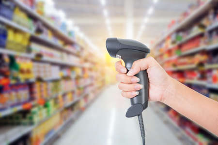 barcode scanner in woman's hand isolated on supermarket background