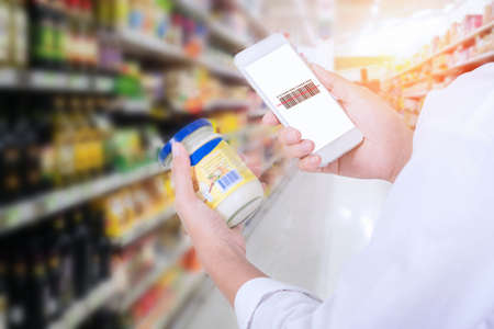 Woman scanning barcode from a label in a supermarket with mobile phone Stockfoto