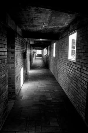 narrow corridor brick wall stone floor black white Stock Photo