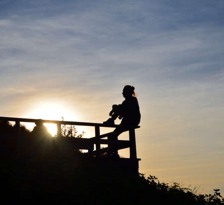 edge: silhouette of lady sitting on the edge
