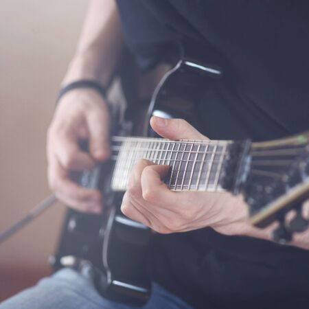 Repetition of rock music band. Cropped image of hands electric guitar player