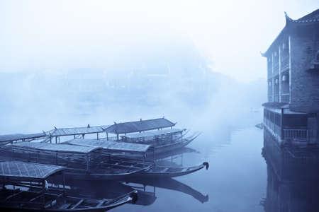 riverside: boat on riverside in fog,chinese phoenix town