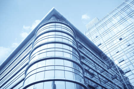 construction companies: modern glass curtain wall of office building with sky background