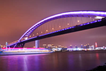 night view of a modern highway bridge with light traces from moving cruise ship in shanghai,China photo