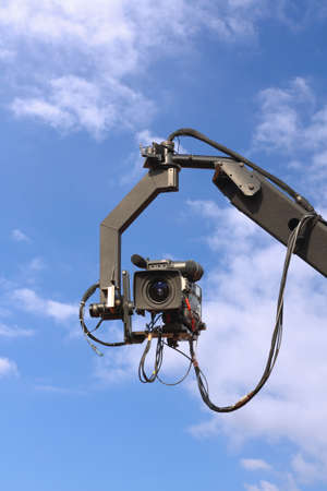 telecast: professional tv camera on a crane with blue sky