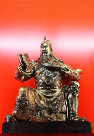 almighty: statua di bronzo di Guan Gong con rosso backgroundGuan Gong � un nome di famiglia nella storia dei caratteri cinesi. � il Dio Onnipotente di protezione e il Dio della ricchezza, il simbolo di coraggio e di giustizia e di fidelizzazione Archivio Fotografico