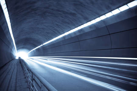 fast lane: traces of light and motion blur of tunnel in blue tone