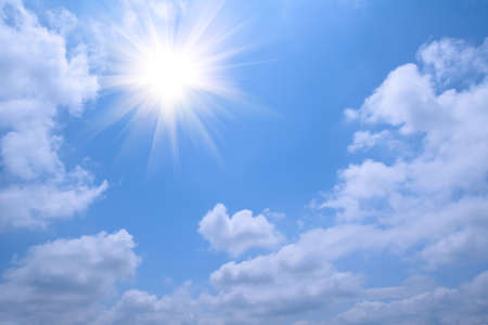 background of blue sky and white cloud and radiant sun Stock Photo