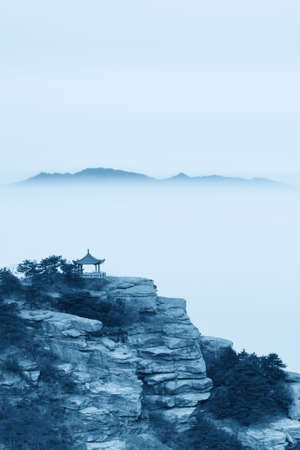 looming: the pavilion of look cloud in chinese lushan and distant mountains