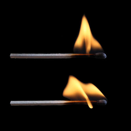 two burning matches with black background  photo