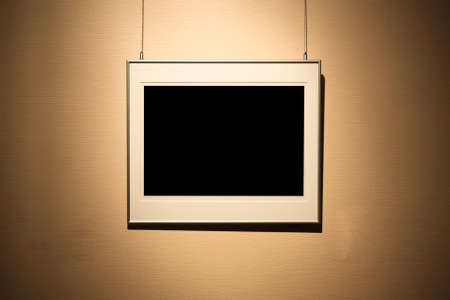 art museum: single empty frame on the spotlight