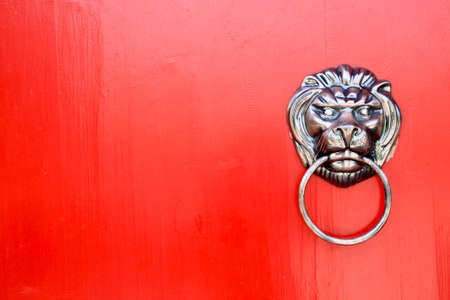 lion knocker on the chinese traditional red door photo