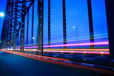 convergence: highway bridge light trails at dusk