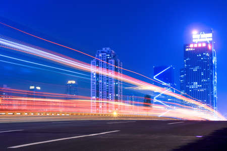 light trails on the highway with modern building background at night  Stock Photo - 10023297
