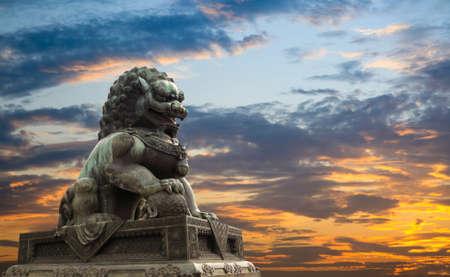 majestuosa estatua del león, con luz puesta del sol, la cultura tradicional china, símbolo de la integridad y dignidad. Foto de archivo