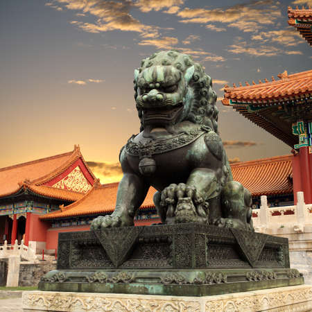 beijing: bronze lion with sunset glow in the forbidden city
