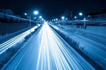 rush hour traffic at night, light trails on the fast lane photo