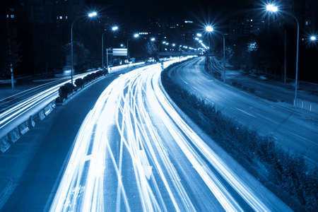 rush hour traffic at night, light trails on the modern city photo
