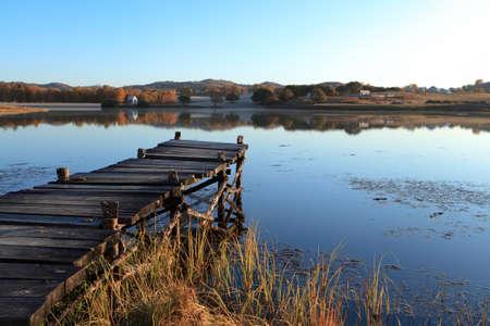 lake shore: wooden pier in tranquil lake at morning