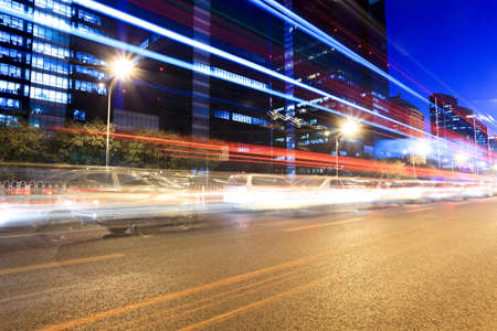 the light trails on the modern building background in rush hour traffic at night photo